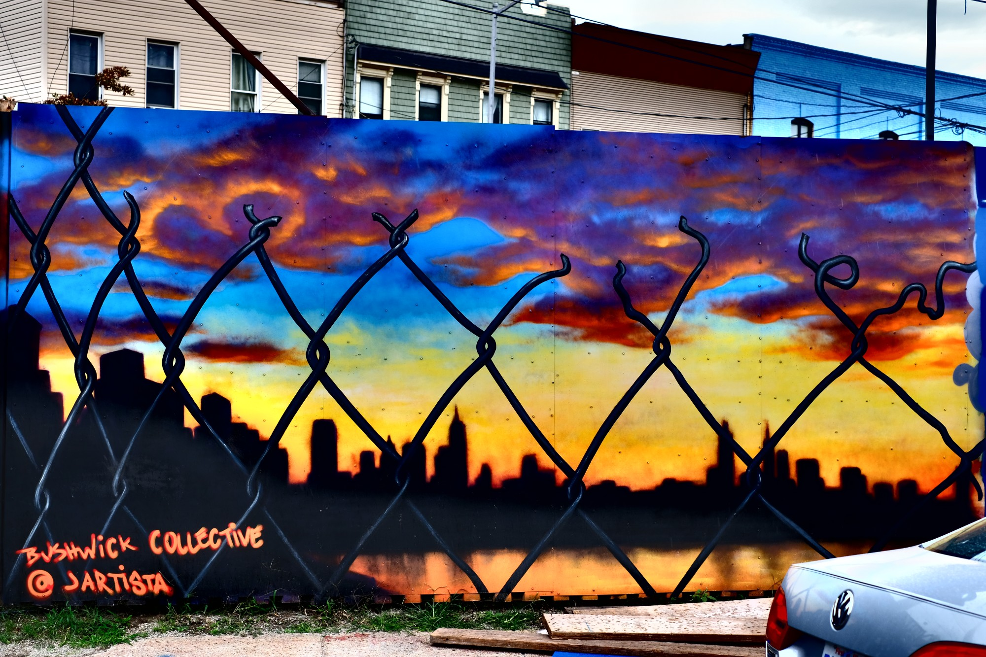Manhattan skyline at sunset, through chain-link fence