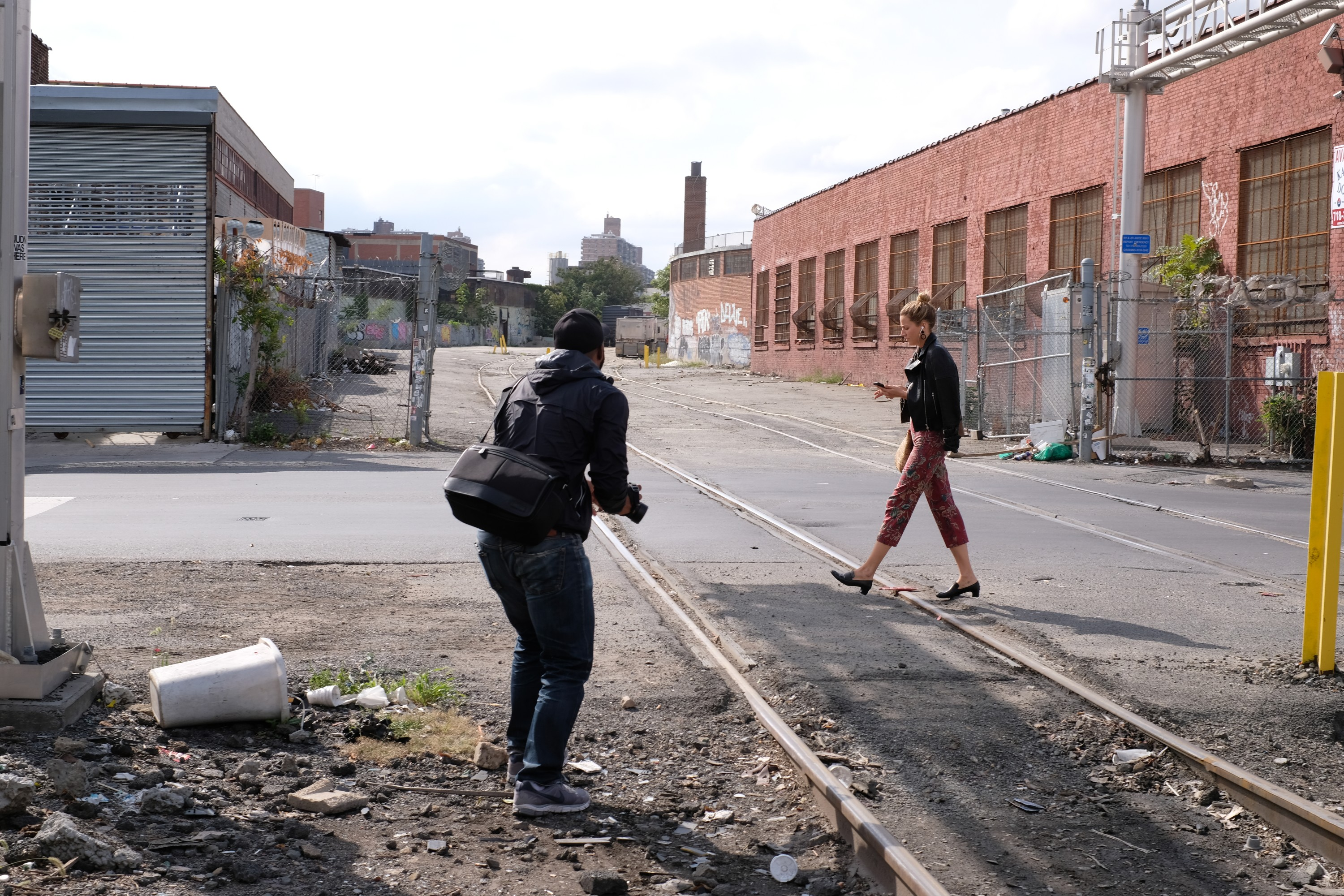 street photographer and woman walkng by train tracks