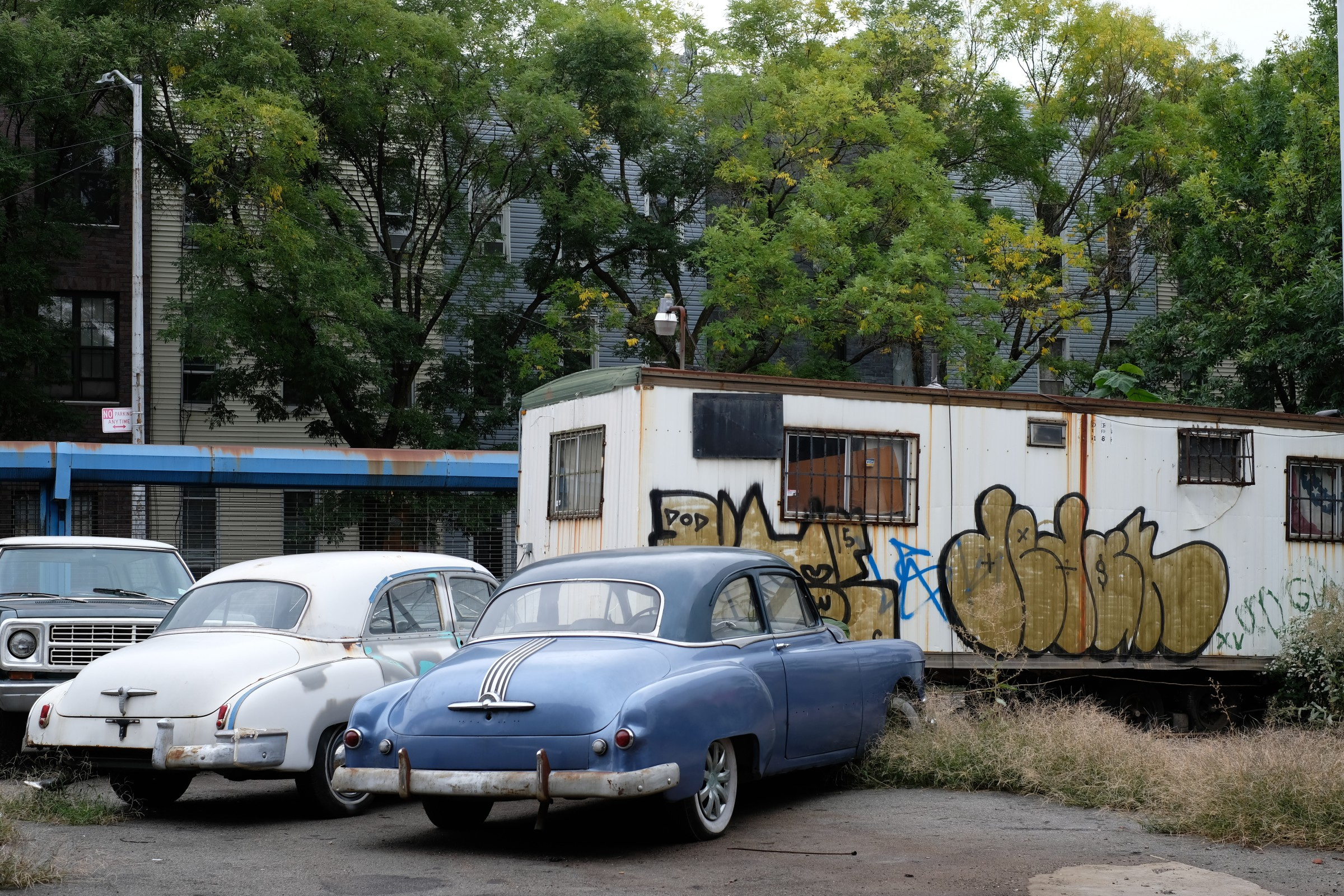 two abandoned 1950s cars and a trailer
