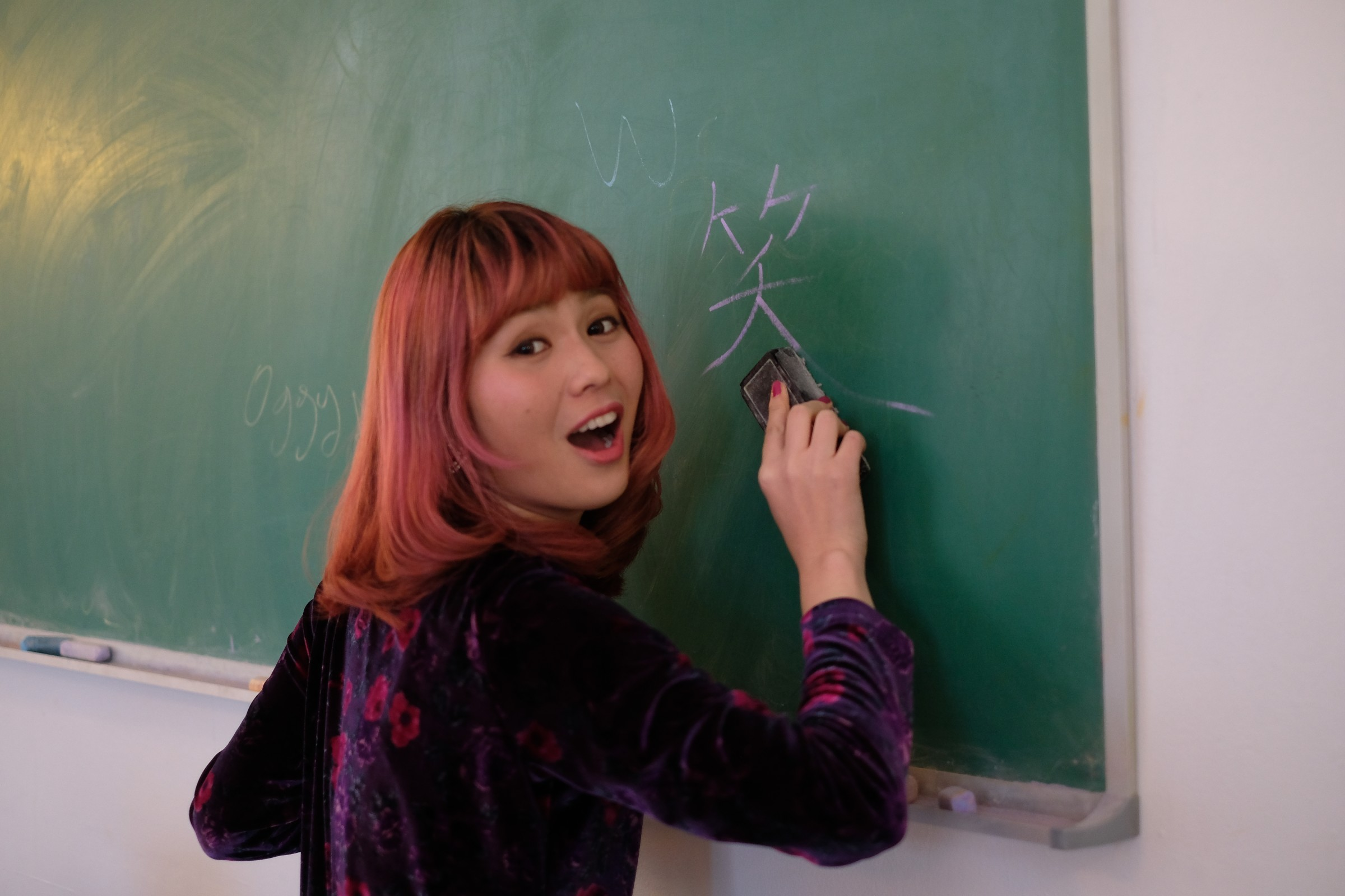 Asian girl writing on chalkboard