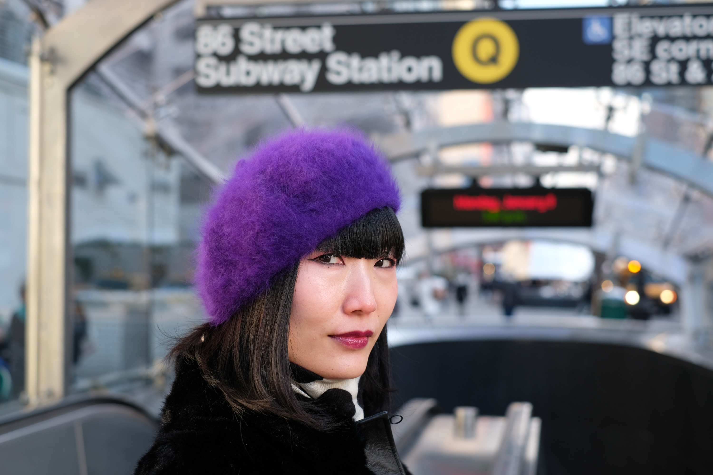 Girl in purple beret in front of subway station