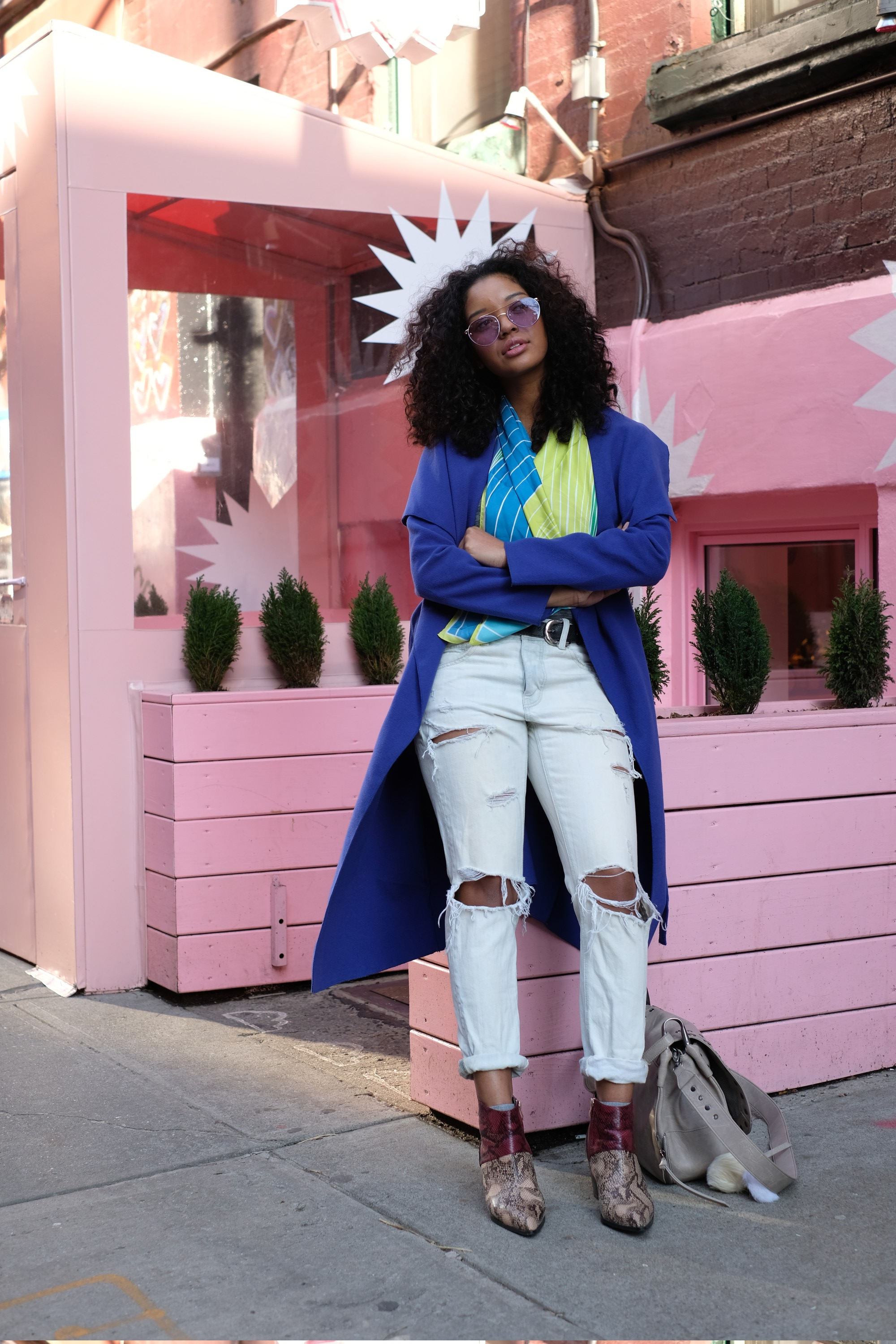 girl in blue coat by pink storefront