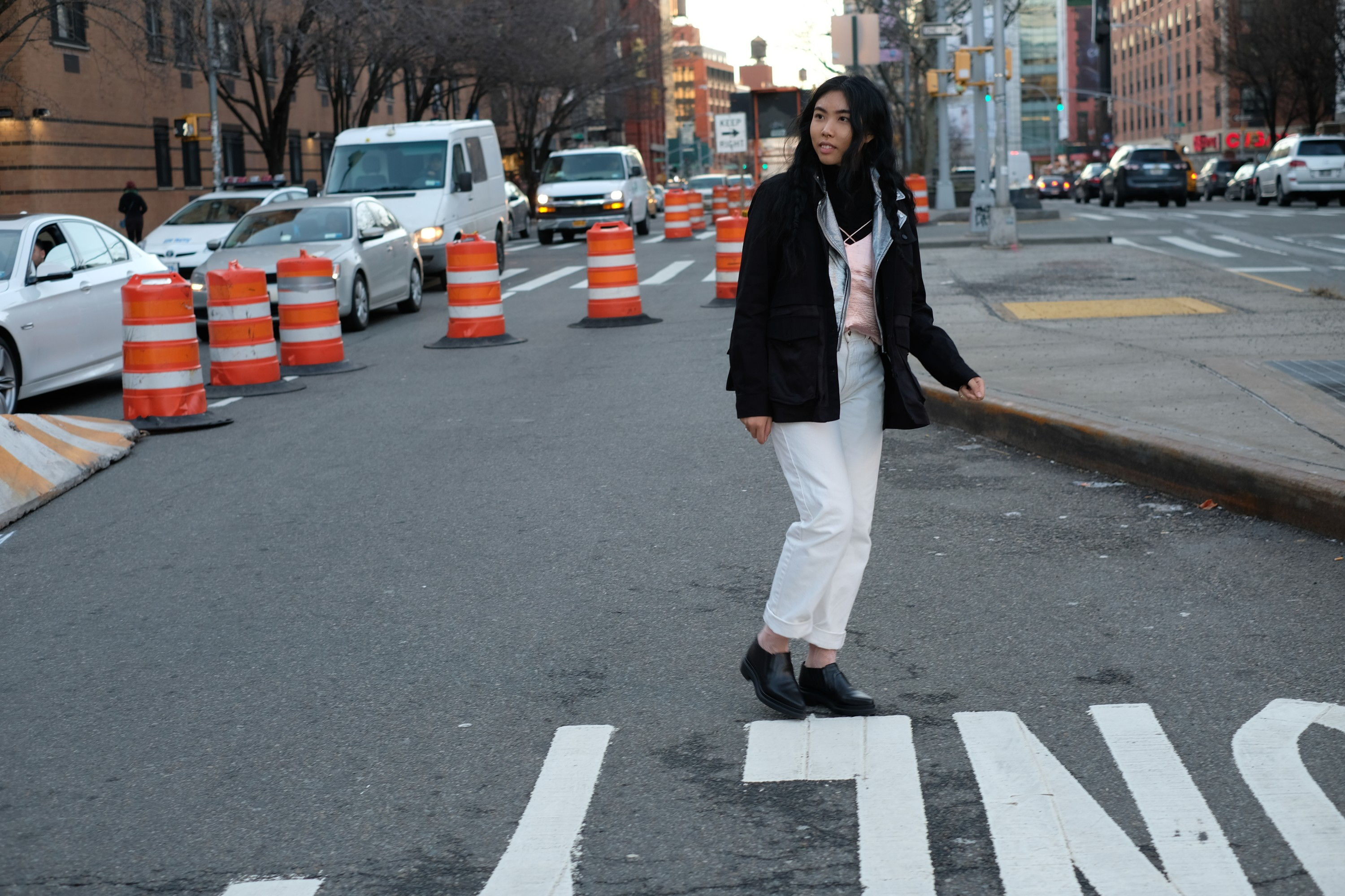 girl in white pants and black jacket crossing the street