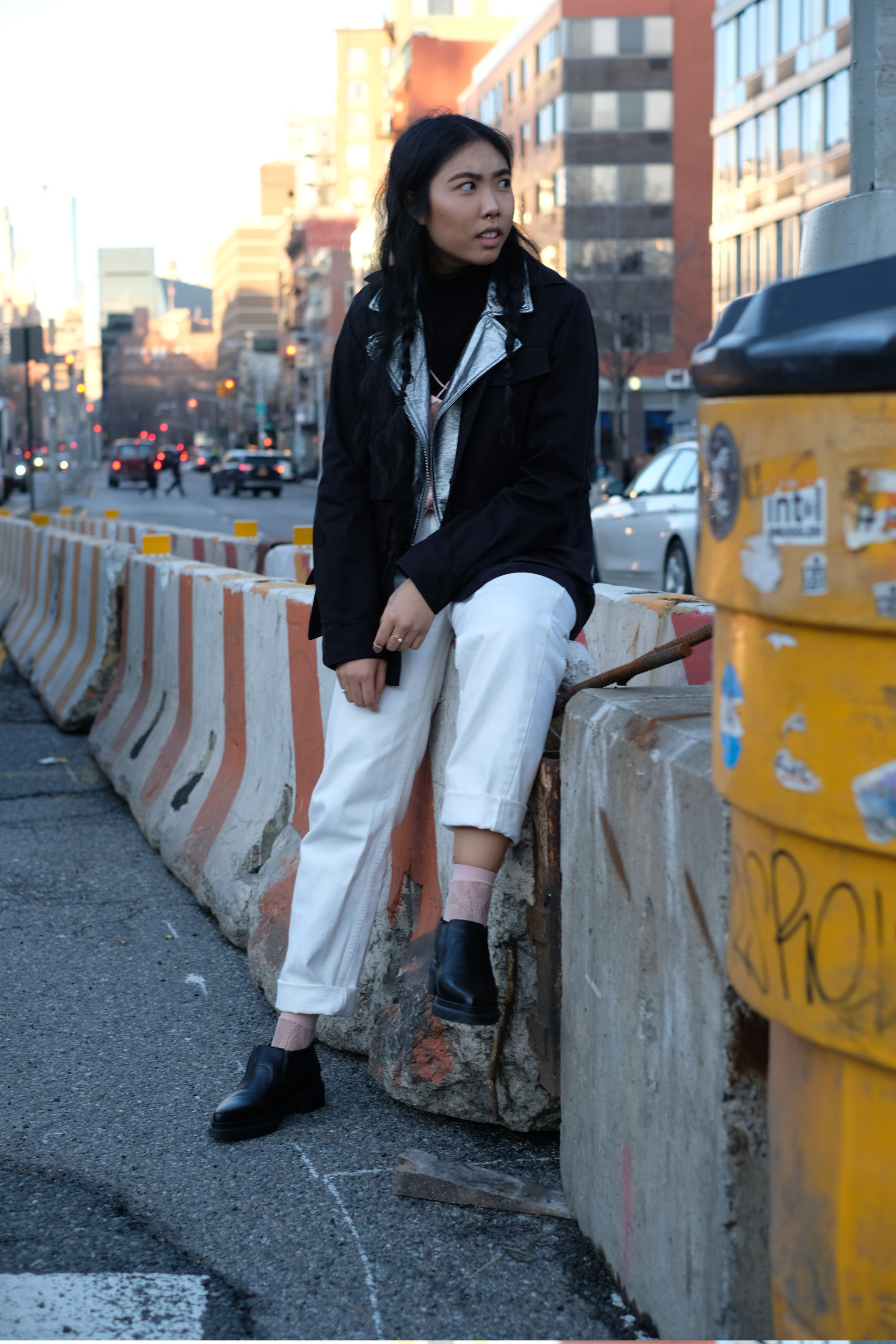 seated Asian girl in white pants and black jacket