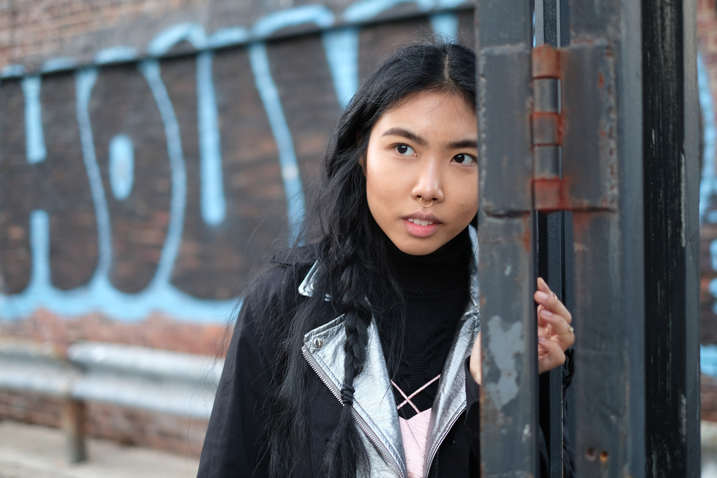 Asian girl by iron fence and graffiti