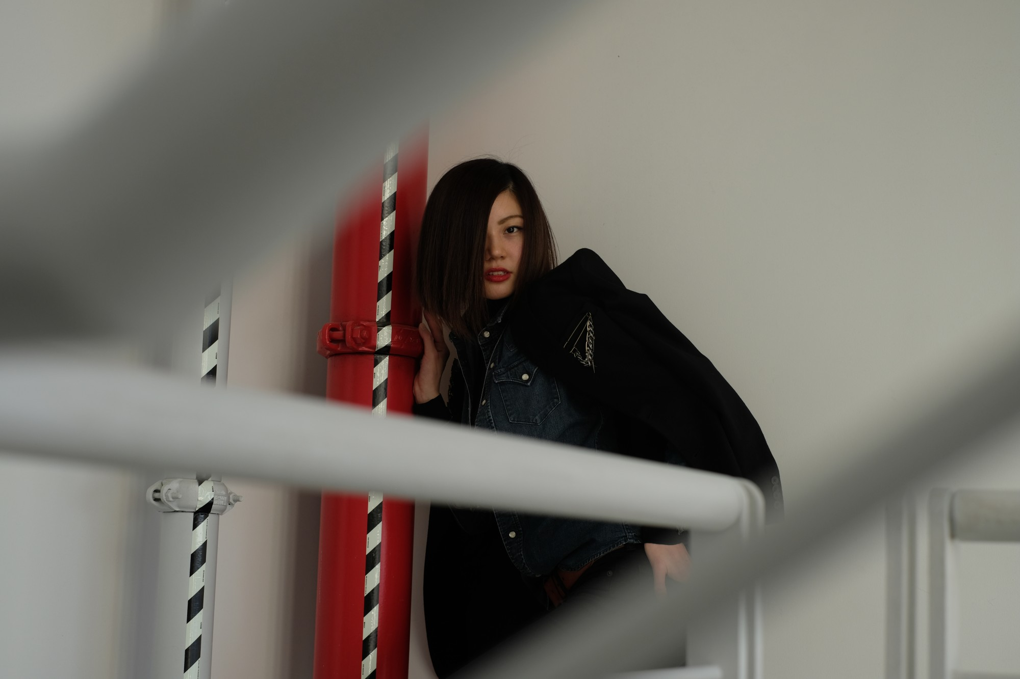 model by red pipe with blurry railings
