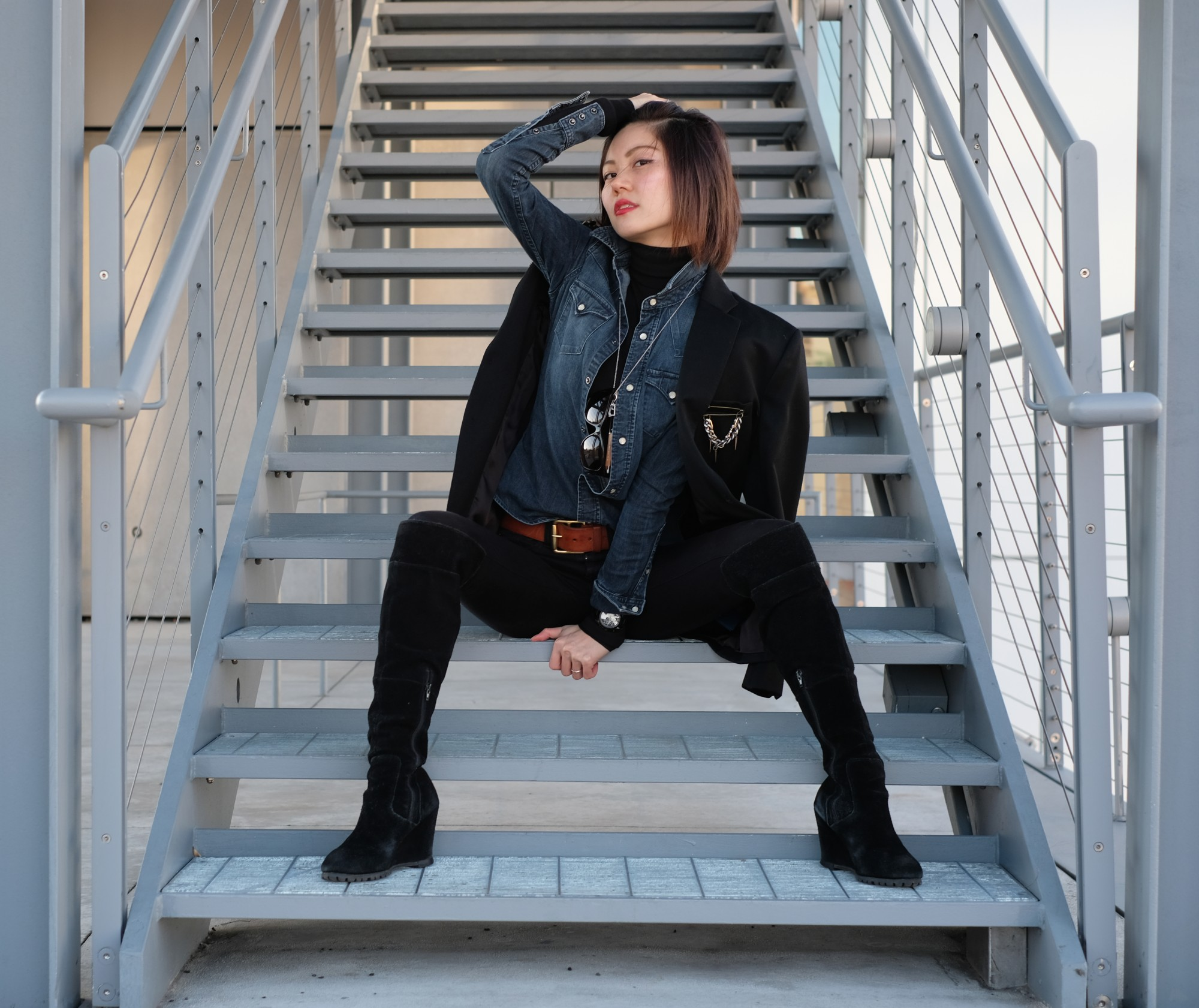 Asian girl sitting on metal stairs