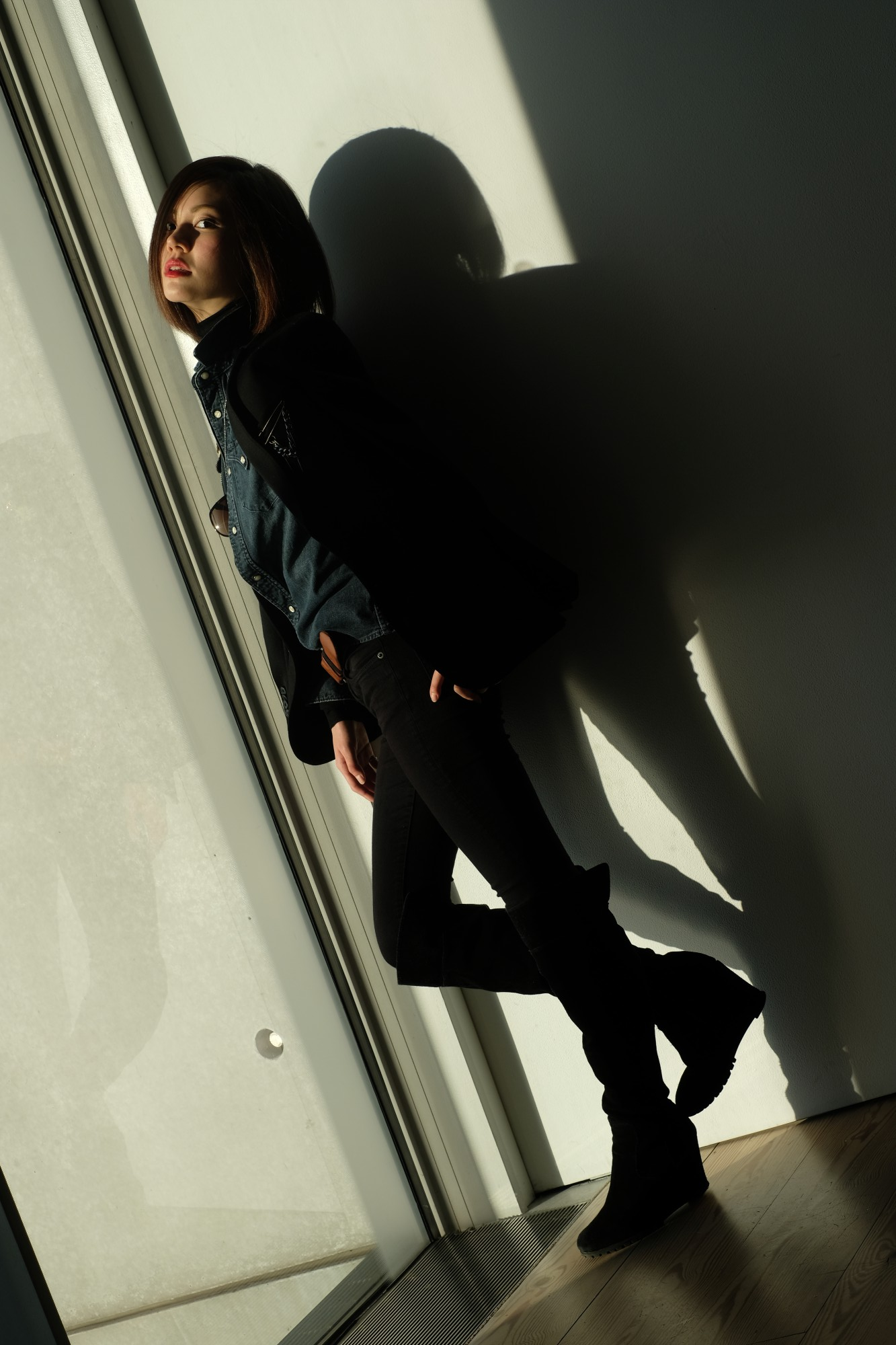 girl standing by window with shadows