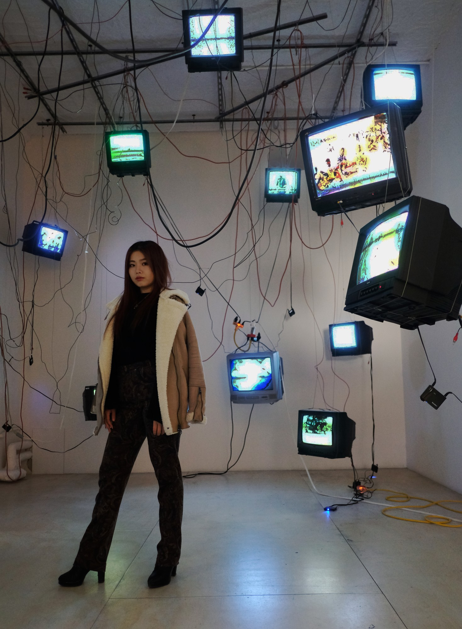 Japanese girl amidst TV screens