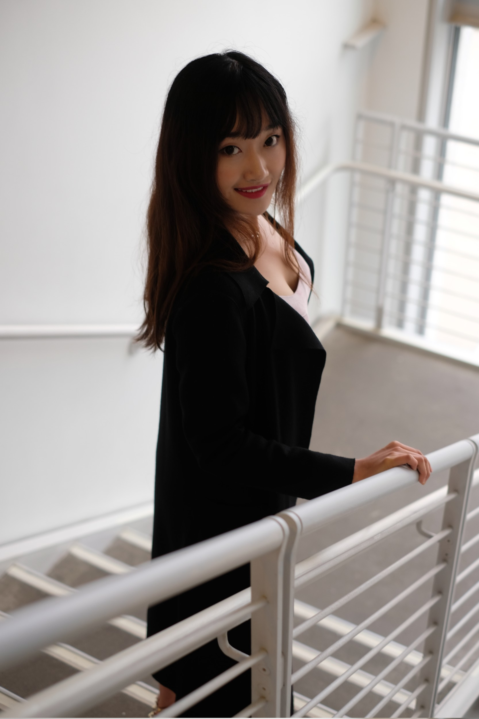 Chinese girl in black coat in stairwell