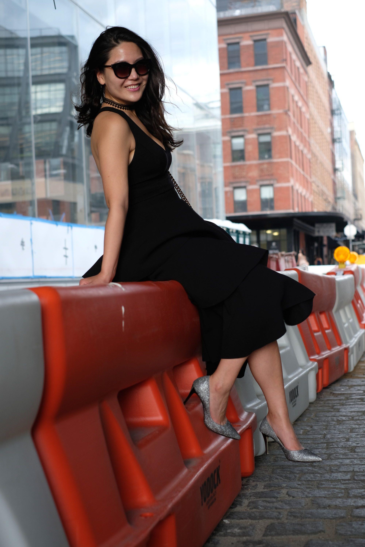 model sitting on construction barrier