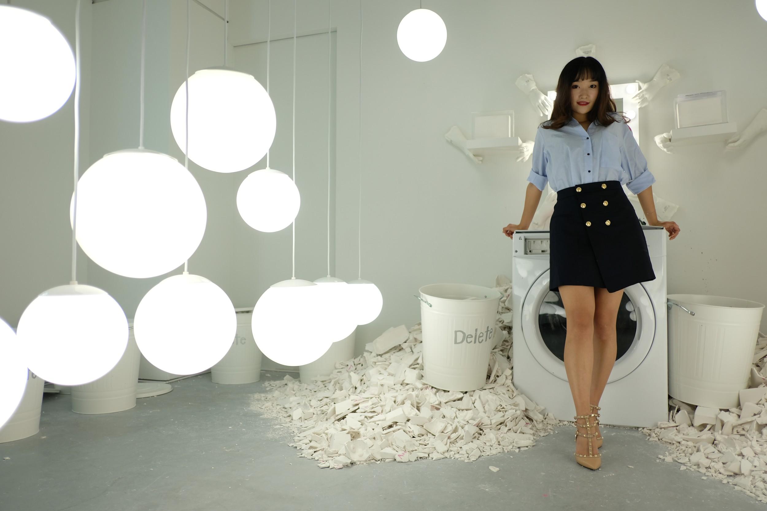 girl in blue skirt in white room